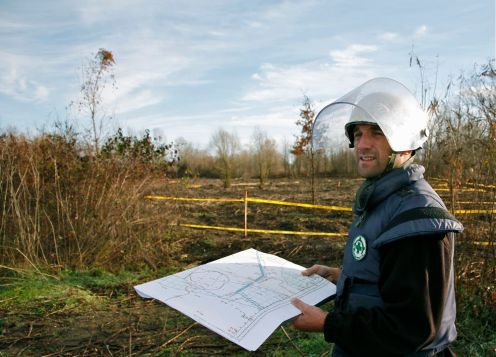 The de-miners and mine detection dog handlers are wearing ballistic vests and helmets. The mine detection dog coordinator Vedad Omerhafisovic is holding the map – the clearance plan of Orašje mine field.