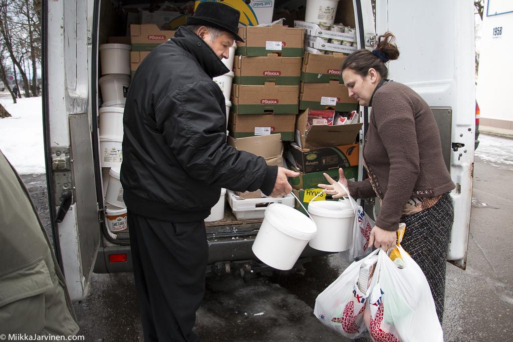 Romaniaktivisti Allan Palm jakaa ruoka-apua Latvian itärajalla.