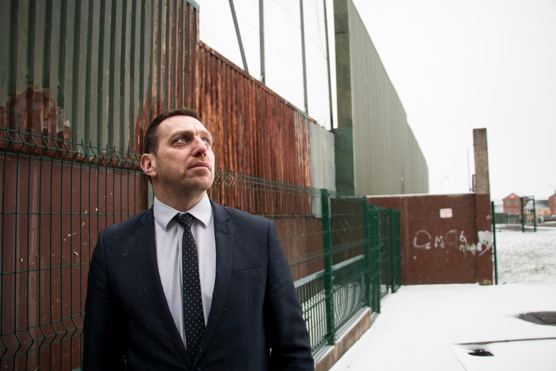 Asianajaja Padraig Ó Muirigh esittelee Belfastin katolisten ja protestanttien asuinalueita erottavaa turva-aitaa.